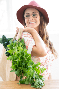 Natalie K. Douglas smiling while carrying a bag of green vegetables and wearing a Boho outfit with glasses